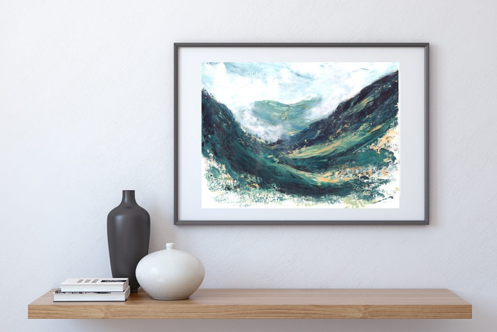 A framed painting of Green, blue and yellow impressionist landscape with sweeping lines of a the Scottish Highlands, Glen Coe Pass, hung on a grey wall above a light wood shelf with a black and a white vase and light coloured books upon it.