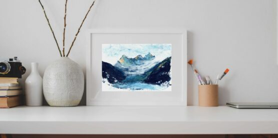 A framed Landscape painting witrh blue mountains capped with orange snowy peaks rests on a grey shelf against a grey wall next to a vase with sticks in it and paint brushes