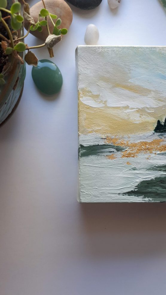 Detail of Painting Landscape sunrise with yellows, greens and taupe on a table next to some gems and a plant