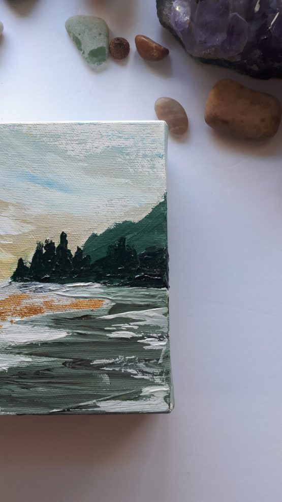 Detail of a Fine Art Sunrise landscape painting with taupe, yellows and greens on a white table next to some stones and a green plant