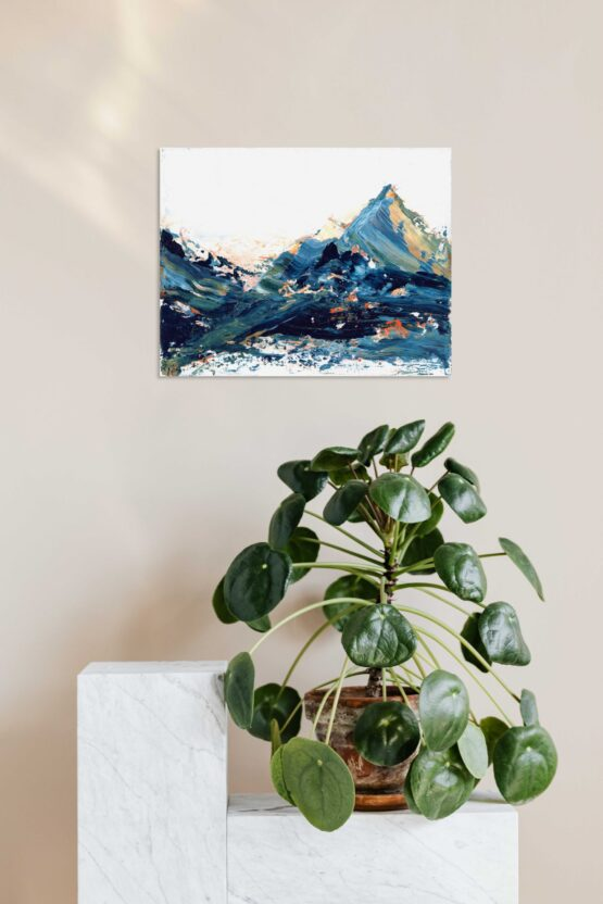Blue, green and hints of orange and yellow marbled abstract mountain against a wispy white cloudy back ground with bits of blue sky peeking through original painting frameless, hung on a beige wall above a white shelf with a green round leafed plant in a brown woven pot