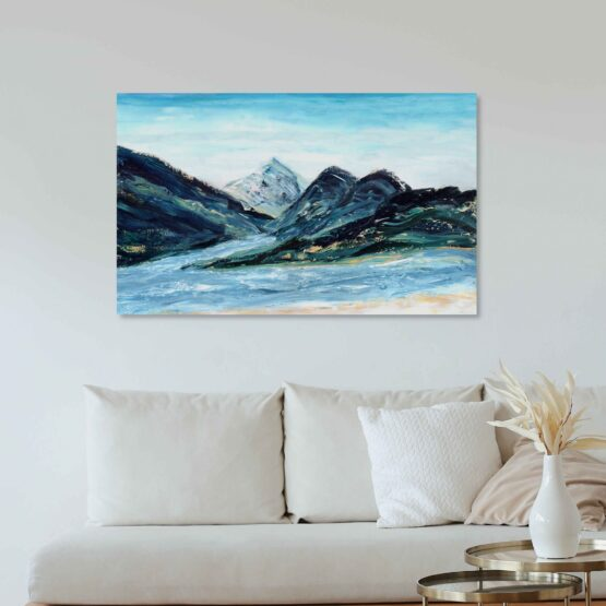Abstract impressionist landscape painting with blue mountain ranges made of marbled paint with light blue skies and a river below hung on a white wall above a white cushioned couch with light wood accents