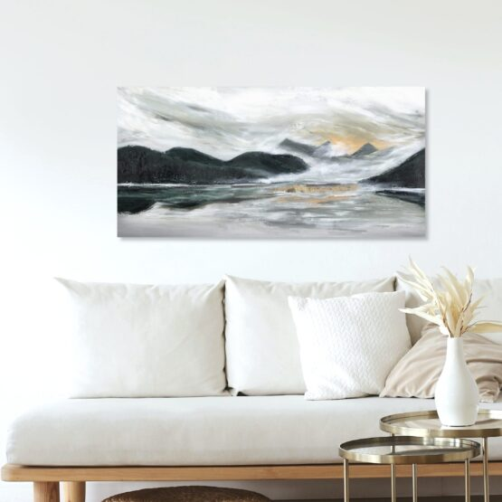 PNW Landscape art painting with dark green rolling mountains and a warm sunset intbetween with grey stormy clouds brewing above, hung on a beige wall above a cream coloured couch with wood frame