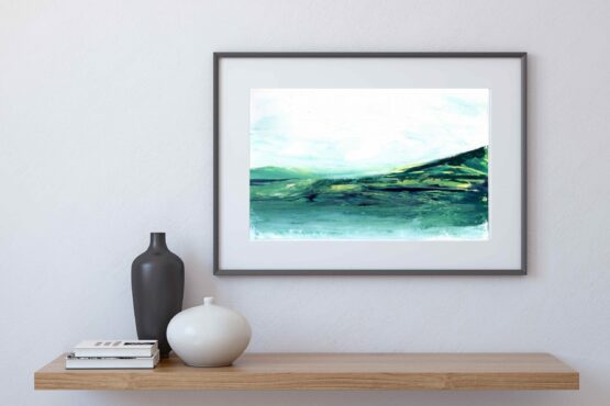 In a black frame, Serene Landscape Painting with brlue and green marbled mountains against a white sky and white water, hung on a white wall above a natural wood shelf with a black vase, a white vase and a small stack of books