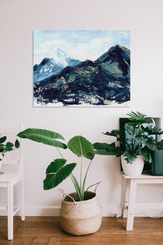 Blue, green and hints of orange and yellow marbled abstract mountain against a wispy white cloudy back ground with bits of blue sky peeking through original painting frameless, hung on a white wall above a white table with a green round leafed plant in a small white plant pot