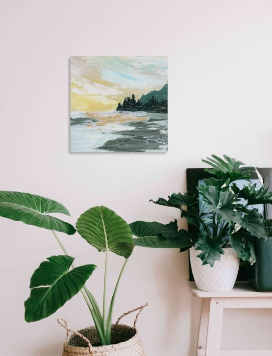 Fine Art print of a sunrise near the beach and mountains painted in an abstract-impressionist way on a beige wall above a leafy potted plant and a small white table with a black picture frame hidden behind the small potted plant
