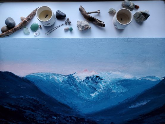large landscape painting with textured flowing blue mountains against a lavendar and pink sunset sky styled on a white table with bits of wood, crystals and leaves surrounding it