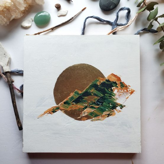 an abstract landscape painting with brown and green marbled paint in the shape of rugged mountains against a white background and a gold leaf moon.
