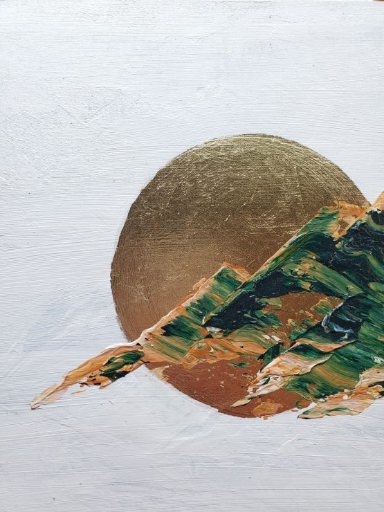 Detail of an abstract landscape painting with brown and green marbled paint in the shape of rugged mountains against a white background and a gold leaf moon.