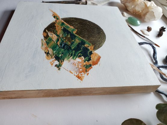 Side view of an abstract landscape painting with brown and green abstract mountains on a white background and gold leaf moon with natural wood edges. The painting is laying on a white table next to a window with a peach coloured quartz crystal, eucalyptus leaf, a small paint brush, blue ribbon and white coloured stones and pinecones.