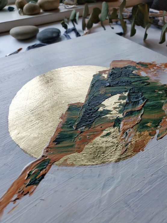 Detail of textured abstract landscape painting with brown and green marbled mountains on a white background and gold leaf moon. the painting is in front of a window in the background that has plants, stones and crystals on the sill of.