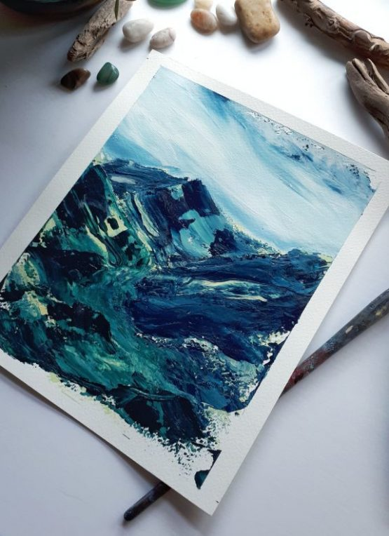A vertical landscape painting with marbled blue and green sweeping hills against a blue and white sky lays on a white table next to a painting brush and some stones and drift wood
