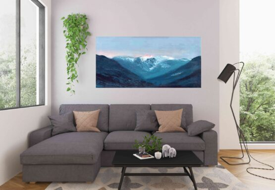 Blue textured Vancouver bc mountains against a lavendar and pink sky wall art print hung on beige wall above grey couch in a livingroom next to plants and a window