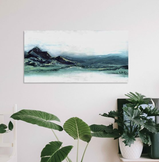 Abstract Mountain landscape print, blue and greens on white wall above plants and a small black photo frame and a white chair